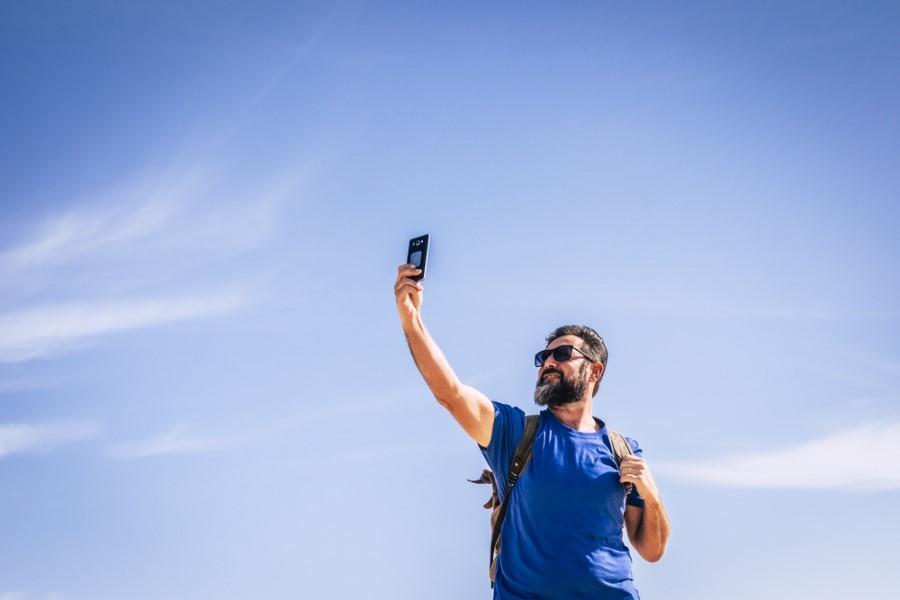 Muž drží telefón nad hlavou a hľadá mobilný signál
