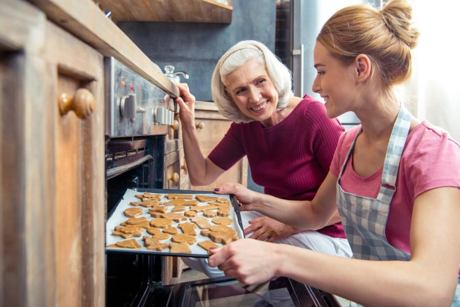 Žena vyberá medovníky z rúry na pečenie