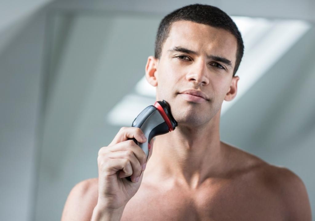 Muž sa holí rotačným holiacim strojčekom